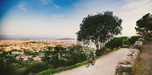 The theme of outdoor activities, sports lifestyle in nature. A man riding a mountain bike cross country on a mountain mountain tibidabo with a view of Barcelona at sunset
