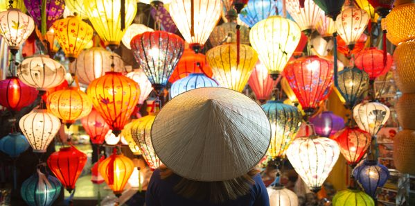 Tourist woman is wearing Non La (Vietnamese tradition hat) and l